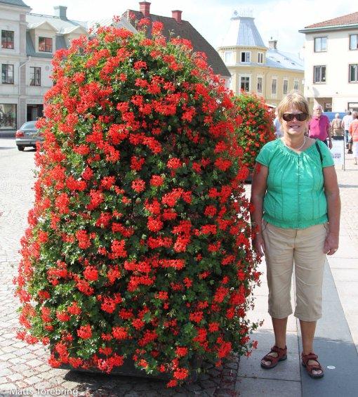 På torget framför kyrkan står Birgtta och dessa blomsterarrangemang