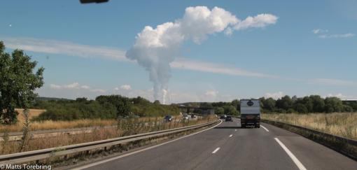 Vi passerar ett stort kärnkraftverk och rökpelarna bildar ett stort moln.