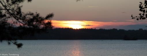 När vi åker hem går solen ned över Assjön