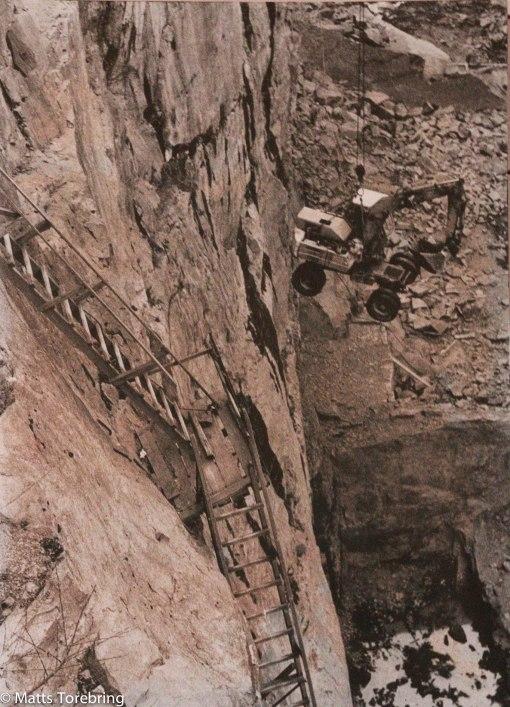 Här hissas en grävmaskin ned.