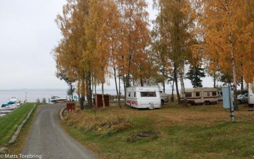 Några husvagnar och husbilar trängs vid stranden